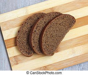 Three pieces of rye bread on a cutting Board.