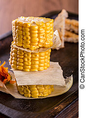 Three pieces of sweet corn placed in a stack