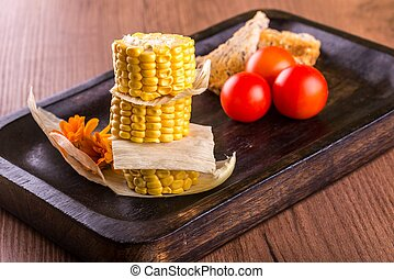 Three pieces of sweet corn with bread and tomatoes