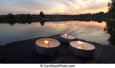 Three pill candles lie on the edge of an old wooden plank ...