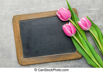 Three pink tulips with an empty chalkboard