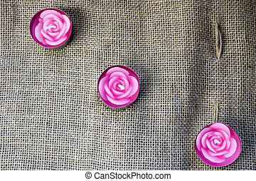 Three pink wax beautiful candles in the form of rose flowers with an unbaked wick on the background of an old brown canvas, harsh, unbleached cloth made from vegetable fibers.