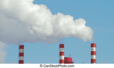 Three pipes with a smoke on blue sky