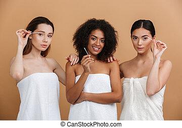 Three pleased women wearing in towels
