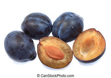 Three plums and one halved - Three whole plums and one ...