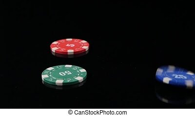 Three poker chips falling in the casino on a black background. 3 pack. Slow motion