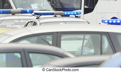 Three police cars on city road - flash lights, telephoto...