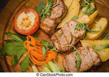 Three pork steaks with fried potatoes and vegetables on a wooden background