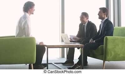 Three positive businessmen gathered together sitting at ...