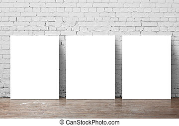 three  poster standing next to a brick wall