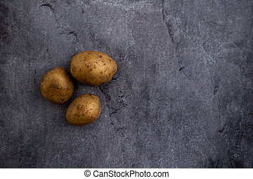 three potatoes on a gray background