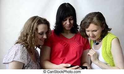 Three pregnant women look at photos