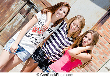 Three pretty teenage young women girl friends with different hair smiling happy & looking at camera