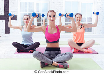 Three pretty women exercising with dumbbells