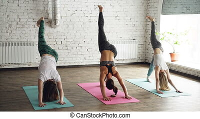 Three pretty young women are doing complex of stretching yoga asanas in light loft style wellness center. Instructor is confident while starting students are awkward.