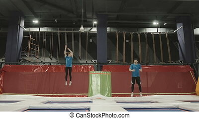 Three Professional gymnasts doing trcks on trampoline synchrone. Amazing tricks by Group of Gymnasts.