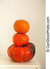 Three pumpkins on a light background