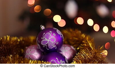 Three purple christmas balls on a bokeh light background