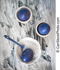 Three purple eggs on a black and white paper background. Salt and ceramic spoon in a salt shaker. Quick protein breakfast