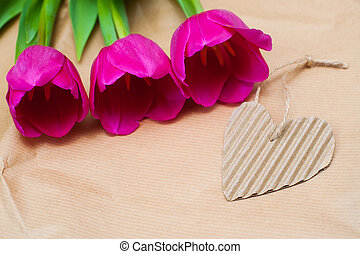 three purple tulip and paper heart with place for text