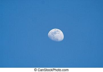 Three quarter moon in blue sky