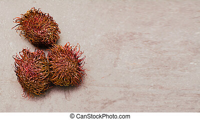 three rambutan fruits on a uniform light background