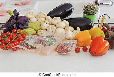 Three raw steaks in vacuum package, vegetables and mushroom. Sous-vide, new technology cuisine.