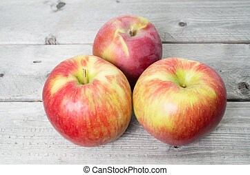 Three red apples on a wooden background