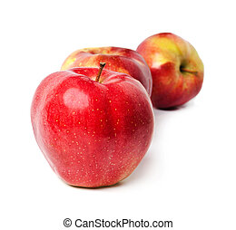 three red apples stand in one row on a white background
