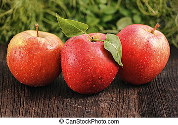 Three red apples with green leafs
