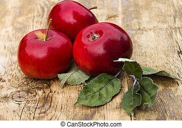 red apples with leaves on a light wooden background