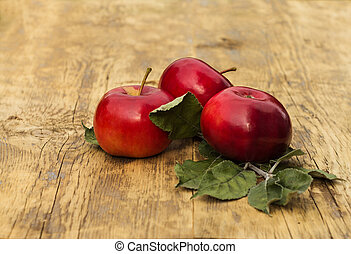 Three red apples with leaves on a light wooden background