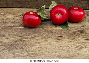 Three red apples with leaves on wooden background