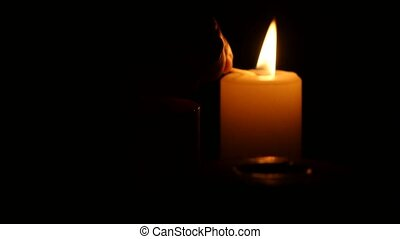 Three red burning candles on black background. Close up -...