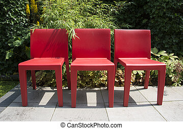 three red chairs in garden