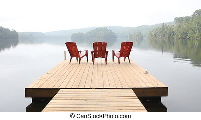 Three red chairs on dock. Misty.