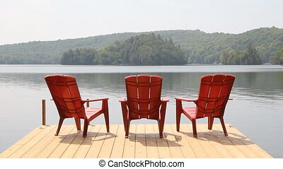 Three red chairs on dock. Sunny.