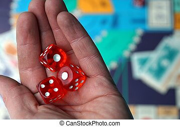 three red dice cubes on the palm above the board game