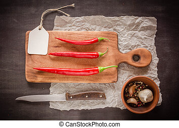 Three red fresh and sharp pepper on a cutting board. Dark background.