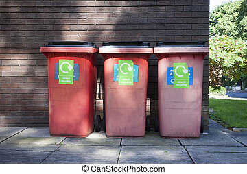 Three red garbage, trash bin eith writing