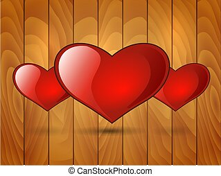 three red glossy heart on a wooden background
