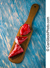 Three red hot chili pepper filled by cheese on wooden spoon