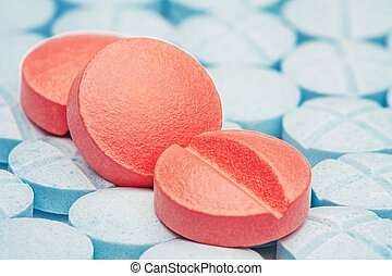 three red medical pills on a background of light blue pills...