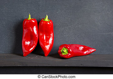 three red peppers on black