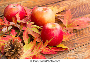 three red ripe apples, pine cones and bright autumn leaves of maple on a wooden background closeup