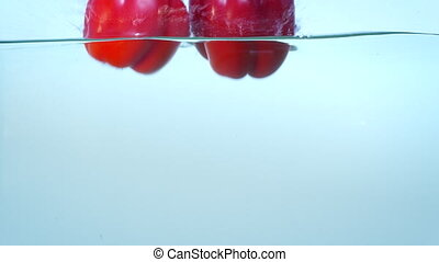Three red ripe bell peppers in water slow motion.