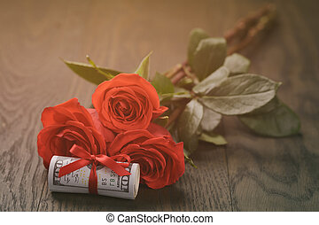 three red roses and bunch of dollars