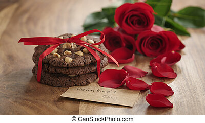 three red roses and homemade cookies on old wood table with paper card for valentines day