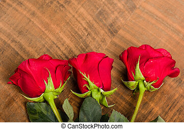 Three red roses laid on a table