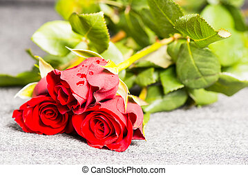 Three red roses on a cloth